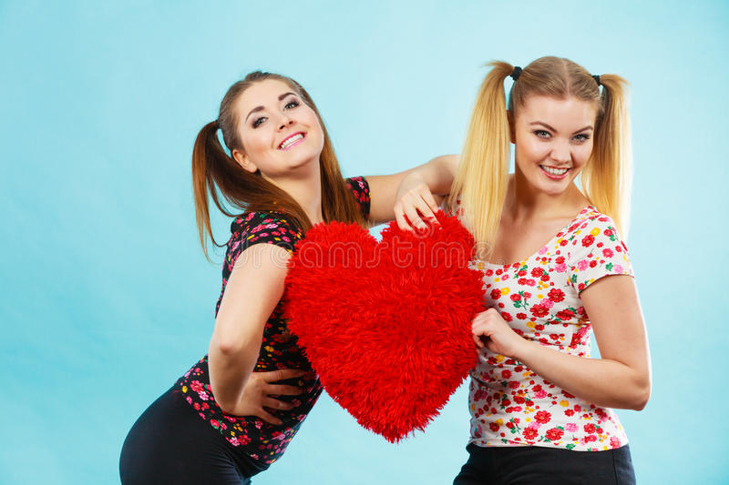 Happy two women holding heart shaped pillow stock images