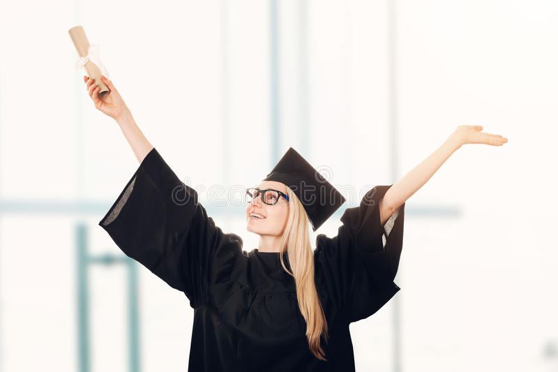 Happy university graduate wearing cap and gown royalty free stock photo