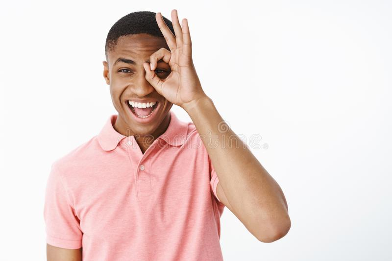 Happy uplifted and charismatic attractive young african american man smiling and laughing joyfully showing zero or okay royalty free stock images