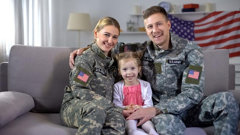 Happy US military family hugging on sofa smiling at camera nation and patriotism. Stock photo stock photos