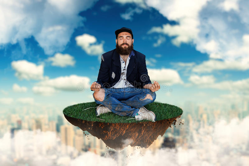 Happy vagrant. Homeless is meditating on flying island in the sky royalty free stock images
