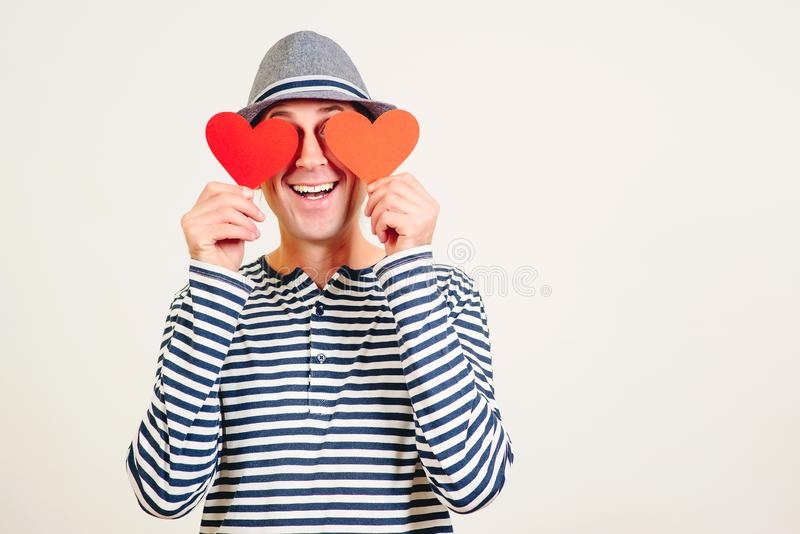 Happy Valentine Day. Man in love. Boyfriend holding heart shaped valentine cards in front of his eyes. Blinded by love. Hipster in. Hat with valentine cards royalty free stock image