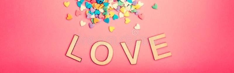 Happy Valentine Day Mooie kaart met kleurrijke hartendoekjes op roze achtergrond Februari populaire vakantie Houten woorden stock foto