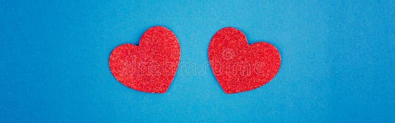 Happy Valentine Day Schitterend kaartbehangsel met twee rode harten in het midden op blauwe achtergrond Begrip liefde en februari stock afbeeldingen