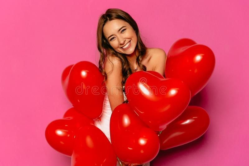 Cheerful woman posing at camera with red balloons. royalty free stock photography