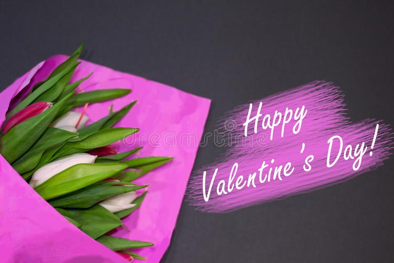 Happy Valentine`s Day. Bouquet of fresh tulip buttons in pink paper on black background. Pink and white flowers lie on table in. Office. Horizontal floral flat stock photography