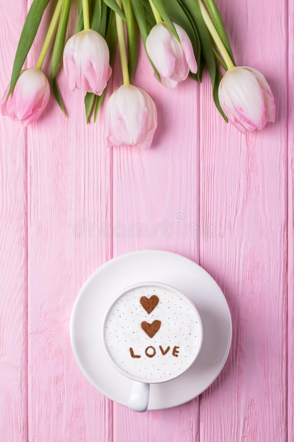 Happy Valentine`s Day. Coffee cappuccino, two hearts, inscription LOVE and pink tulips on a pink background. Top view, free space royalty free stock photos