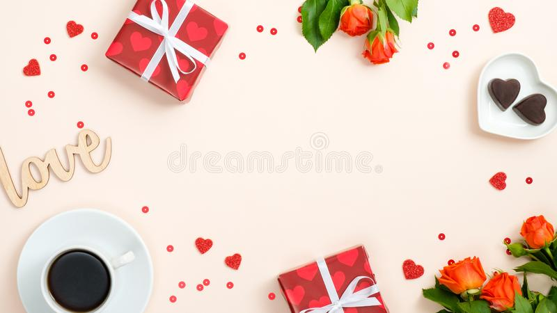 Happy Valentine`s Day frame. Valentine card with gifts, red hearts, coffee cup, candy, roses on pastel beige background. Flat lay. Top view, overhead stock photography