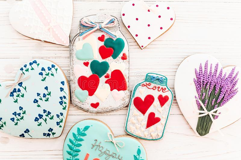 Happy valentine`s day greeting card. jar with colorful cookie he. Arts on white rustic wooden background flat lay. space for text . mock-up. happy mother`s day royalty free stock image