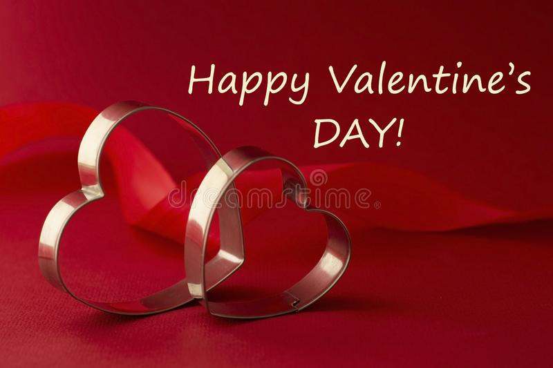Happy Valentine's Day Greeting card. Two red heart shaped cookie cutters on beautiful red background royalty free stock images