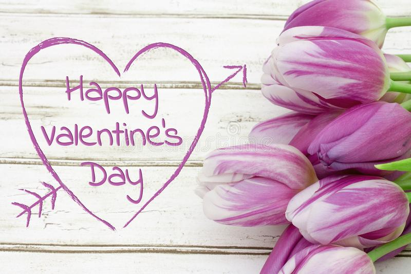 Happy Valentine`s Day greeting with tulips on weathered wood. And text Happy Valentine Day in a carved heart stock images