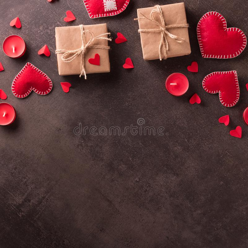 Happy Valentine`s Day. Handmade jewelry red hearts, gifts in craft paper and candles on dark background royalty free stock photo