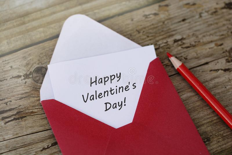 Happy Valentine's Day inscription - red envelope with blank card on wooden background with copy space, and red pencils stock image