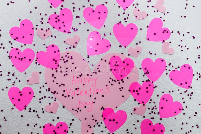 `Happy Valentine`s Day` message on a big pink hart with a lot of pink harts and sparkles around it stock photography