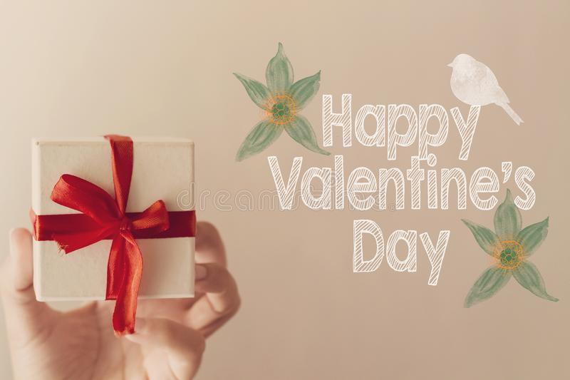 Happy Valentine`s day message with white gift box with red ribbon hold on hand woman royalty free stock photo