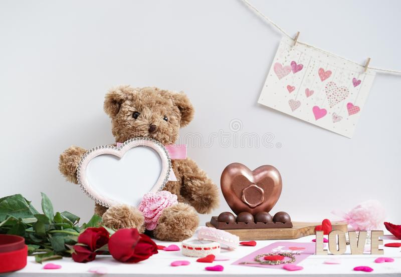 Happy Valentine`s day. Teddy bear plush doll holding an empty beautiful pink heart frame for insert your personal message or phot royalty free stock images