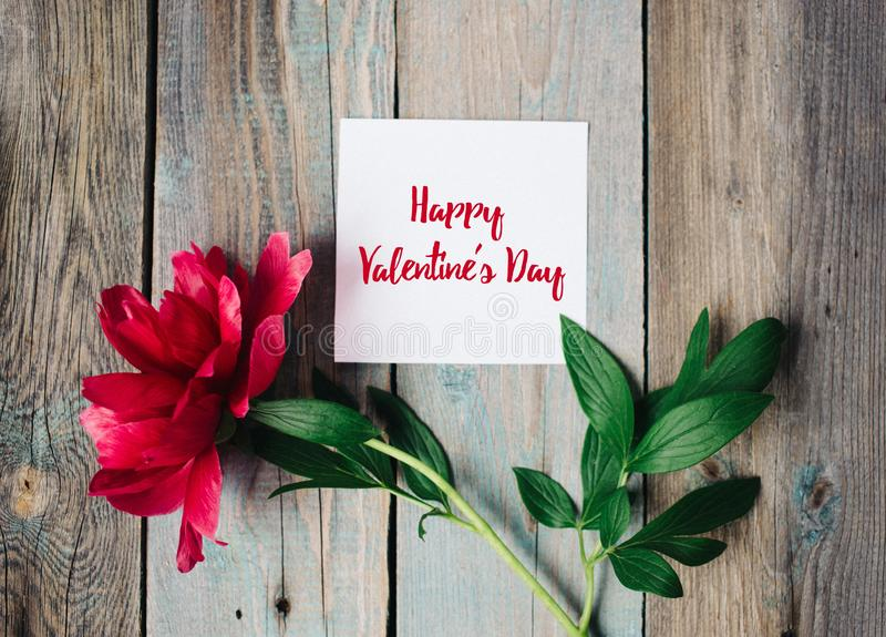 Happy Valentine`s day text on sheet of paper, red flower on old rustic wooden background stock image