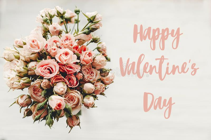 Happy Valentine`s Day text sign on pink roses bouquet on white background, top view. Valentines day floral greeting card stock photos