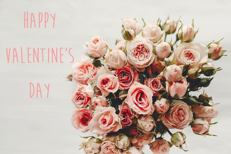 Happy Valentine`s Day text sign on pink roses bouquet on white background, top view. Valentines day floral greeting card stock photography