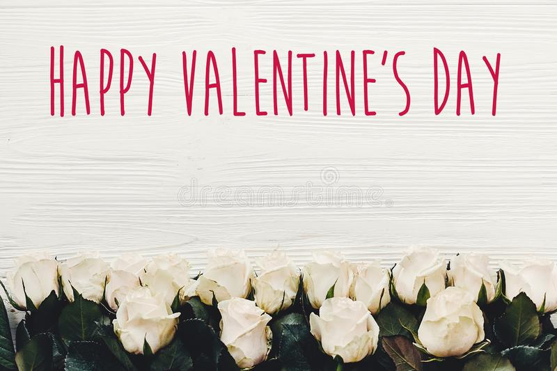 Happy Valentine`s Day text sign on white roses on wooden background, flat lay with space for text. Valentines day floral greetin. G card royalty free stock image