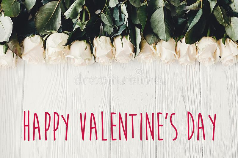 Happy Valentine`s Day text sign on white roses on wooden background, flat lay with space for text. Valentines day floral greetin. G card stock photos