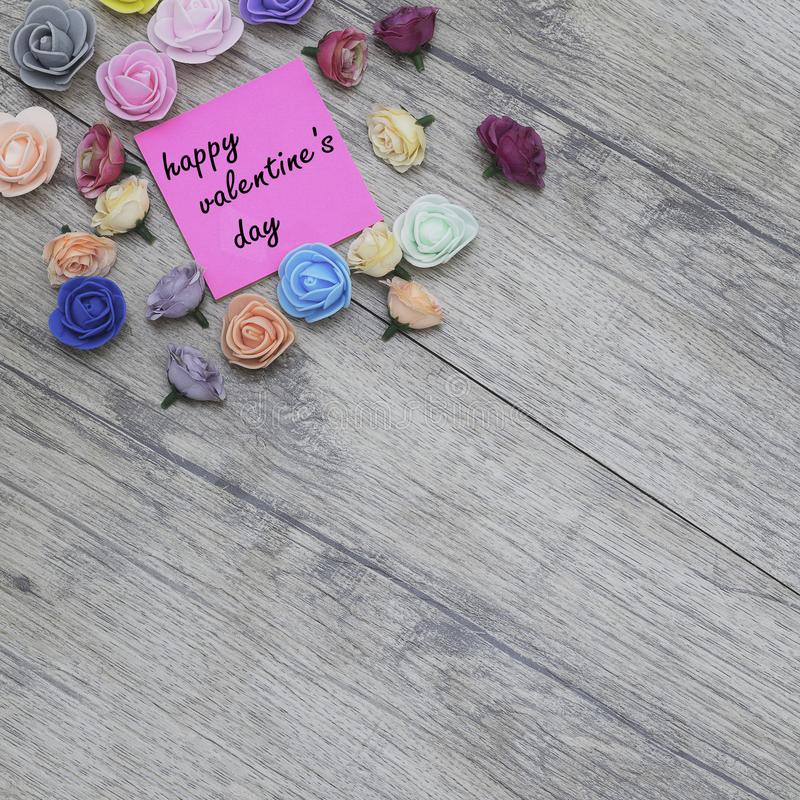 Happy Valentine`s day text on sticker. flowers on wood background. stock image