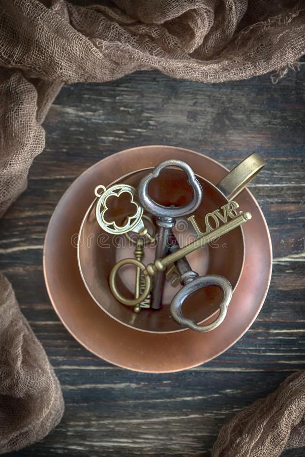 Happy Valentine`s Day! Vintage copper cup and key Love on the old wooden background. Top view royalty free stock photos