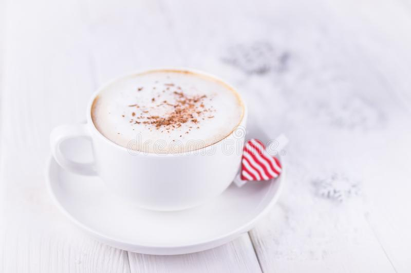Happy Valentine`s day. White cup with cappuccino and red heart on a white wooden background. Free space stock images
