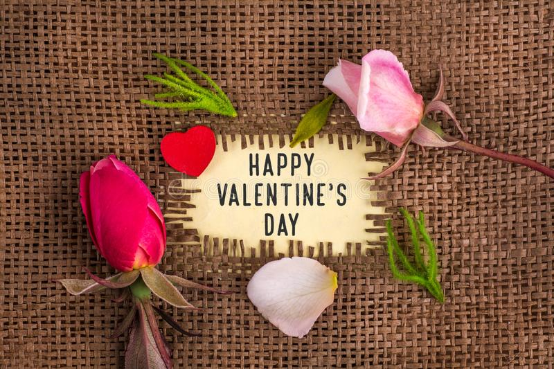 Happy valentine`s day written in hole on the burlap. With rose flowers and wooden red heart stock photos