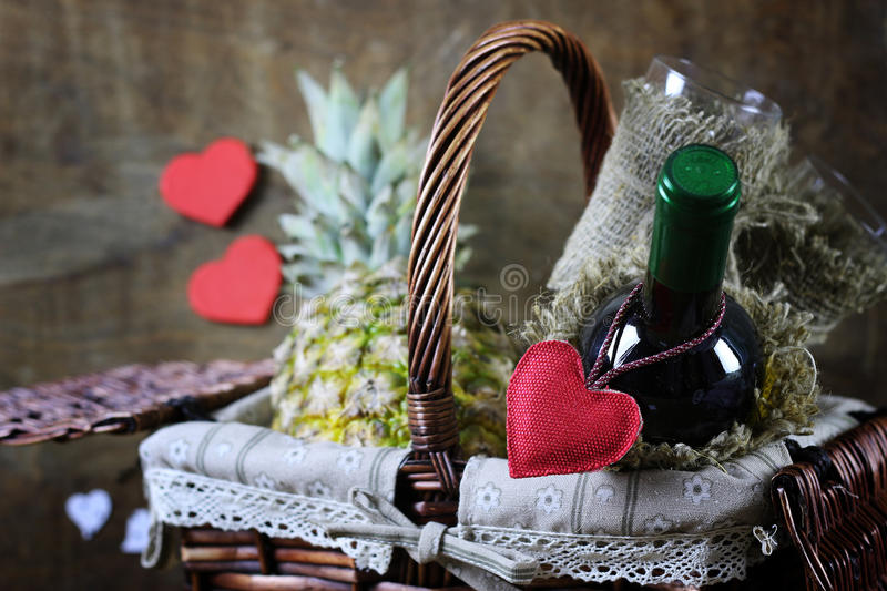 Happy valentine wine bascet. Decoration with a symbol of warmth and love of a small paper heart royalty free stock photography