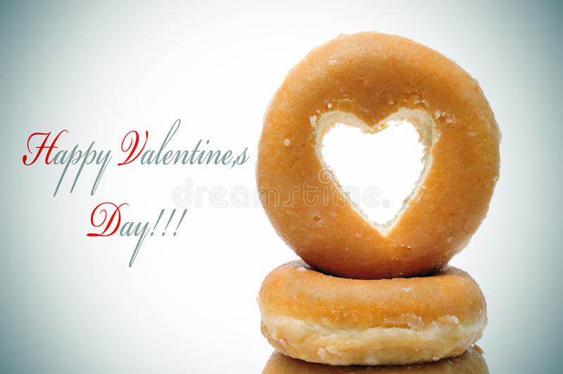 Happy valentines day. And a pile of donuts with a heart shaped hole royalty free stock photo