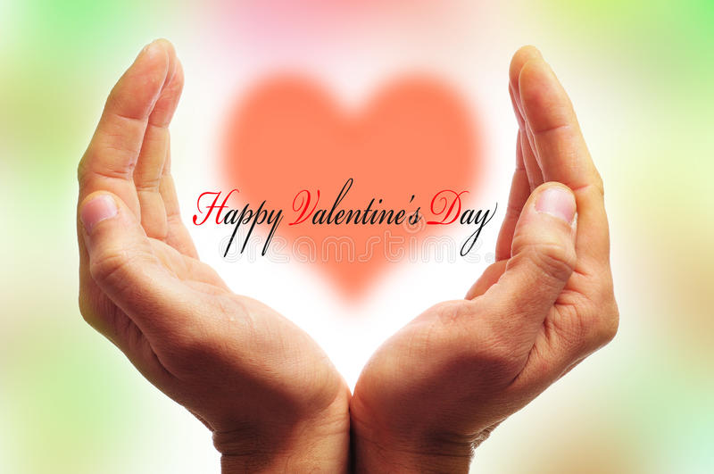 Happy valentines day. Man hands forming a cup and the sentence happy valentines day with a heart in the background royalty free stock photography