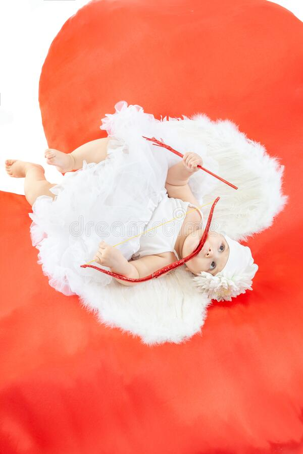 Happy Valentines Day. Angel baby from heaven at the big red heart. Cupid in white wings with bow and arrows stock photography