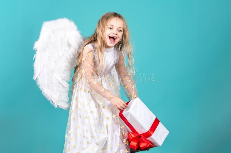 Happy Valentines Day. Angel child from heaven gives you gift. A ngel. Cute toddler girl in white wings as Cupid royalty free stock images