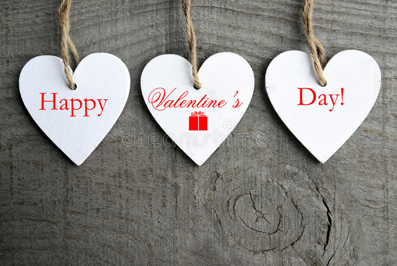 Happy Valentines Day background. Decorative white wooden hearts on grey rustic wooden background with copy space. royalty free stock images