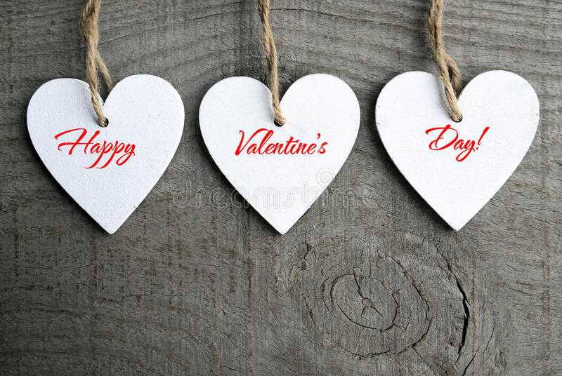 Happy Valentines Day background. Decorative white wooden hearts on grey rustic wooden background with copy space. stock image