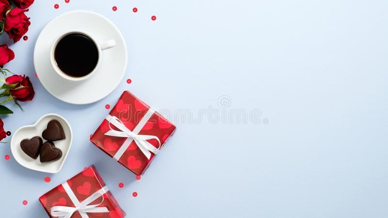 Happy Valentines Day banner. Top view coffee cup, red presents, sweet candy and roses flowers on blue background with copy space. stock photography