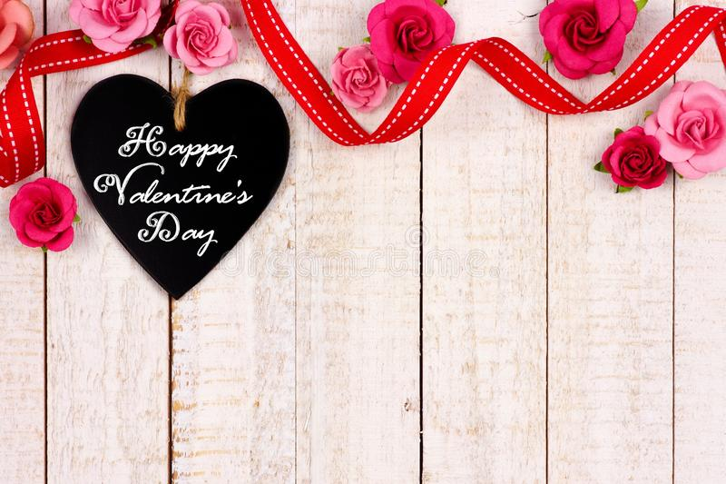 Happy Valentines Day chalkboard tag with ribbon and flower border on white wood. Happy Valentines Day message on a heart shaped chalkboard tag with ribbon and royalty free stock photos