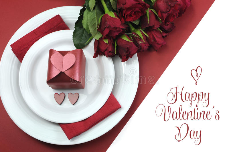 Happy Valentines Day dining table setting, with red hearts, gift, and red roses. With greeting stock photo
