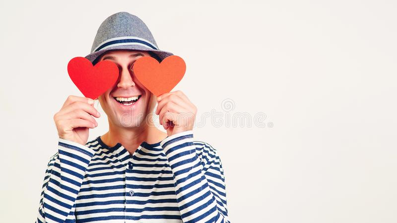 Happy Valentines Day. Funny man covers eyes with red hearts. Happy man in love. Romantic guy holds valentine cards. Be my stock photography