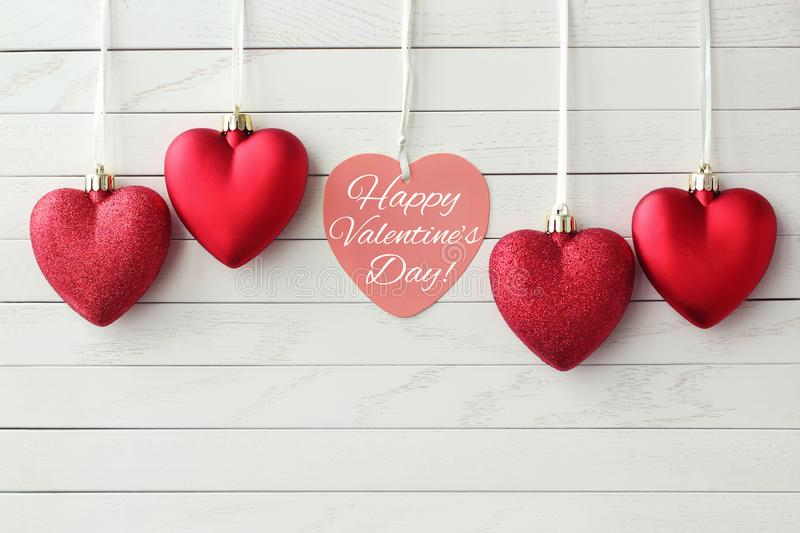 Happy Valentines Day greeting card. Beautiful red hearts. Hanging on wooden background. St Valentine`s Day or Love concept royalty free stock photo