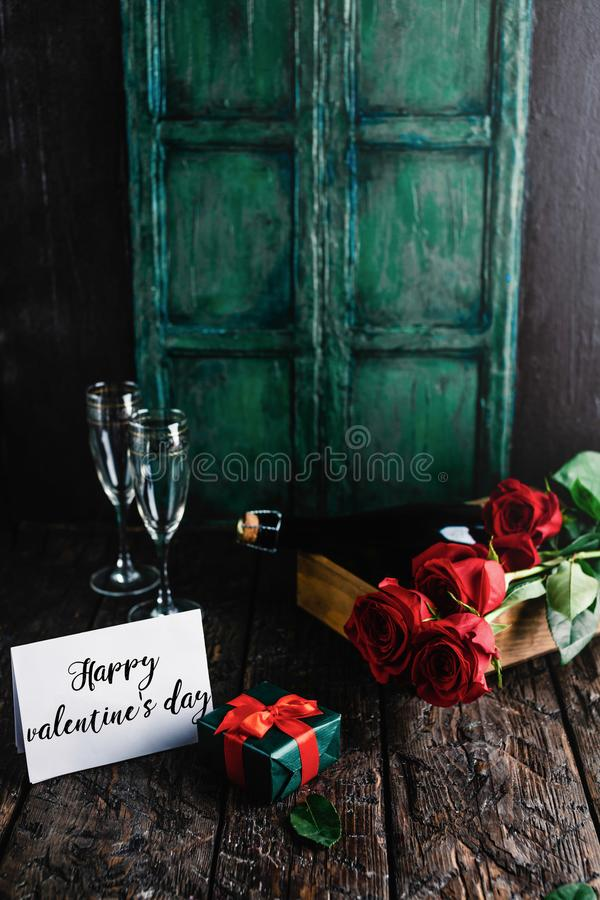 Happy valentines day greeting card, present, red roses and champagne bottle stock image