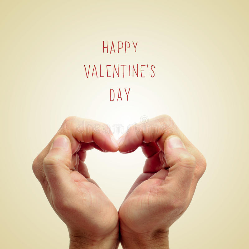 Happy valentines day. The hands of a young man forming a heart and the sentence happy valentines day written on a beige background royalty free stock photos