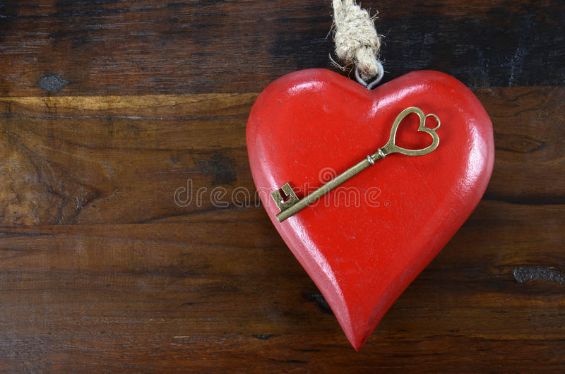 Happy Valentines Day key to my heart concept. With large hanging heart on dark wood background royalty free stock photography