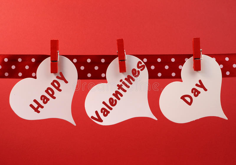 Happy Valentines Day message greeting written across white heart tags hanging from red pegs on a line
