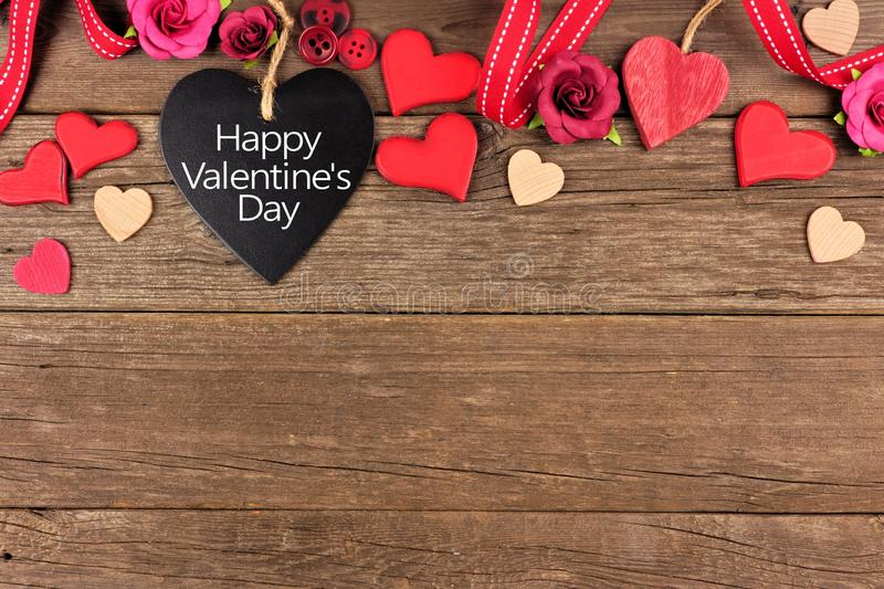 Happy Valentines Day heart shaped chalkboard tag with border against rustic wood. Happy Valentines Day message on a heart shaped chalkboard tag with ribbon and royalty free stock image
