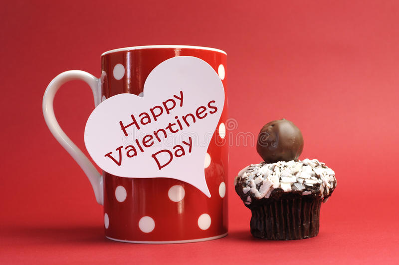 Happy Valentines Day message on red polka dot mug with chocolate cupcake. Against a red background for a bright, fun and cheerful Valentines Day stock image