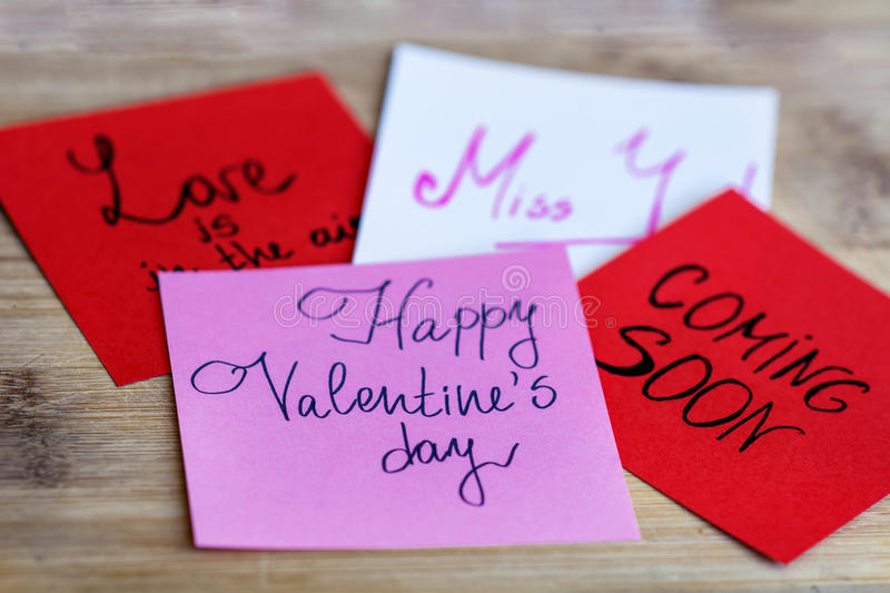HAPPY valentines day pink greeting cards on a wooden background. HAPPY valentines day pink note ,love is in the air red note ,miss you white note ,coming soon royalty free stock images