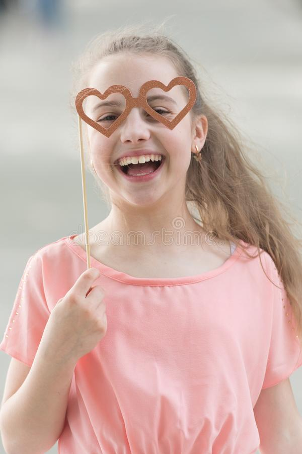 Happy valentines day. Small child with happy smile and funny look through heart shaped glasses. Happy little girl royalty free stock photo