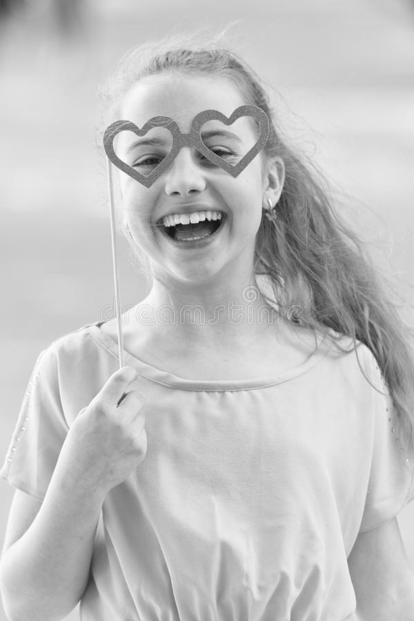 Happy valentines day. Small child with happy smile and funny look through heart shaped glasses. Happy little girl stock photos